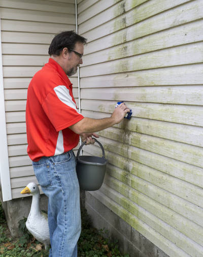 grime coated siding being cleaned