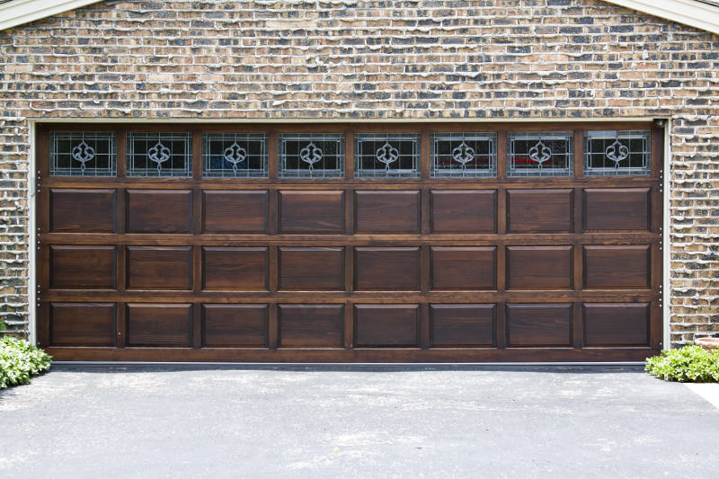 a wood garage door on a brick house